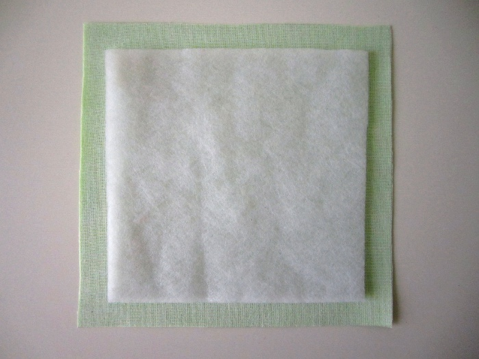 Centrer le molleton sur l'envers de la pièce, côté rugueux thermocollant contre l'entoilage précédemment appliqué.